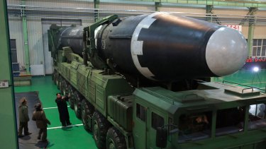 North Korean leader Kim Jong-un, third from left, and what the North Korean government calls the Hwasong-15 intercontinental ballistic missile.