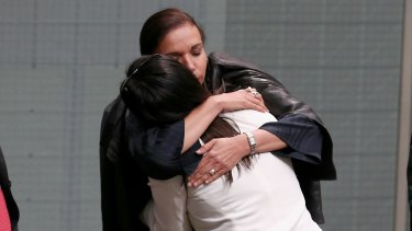 Anne Aly embraces Labor MP Emma Husar after Husar spoke about her experience with family violence.