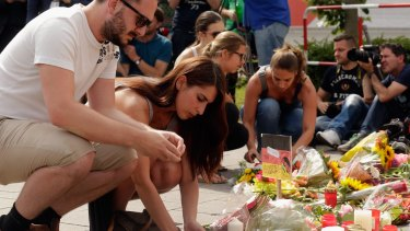People lay flowers and candles outside the OEZ shopping centre.