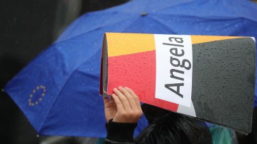 A supporter uses a sign to shield the rain during an election campaign rally for Angela Merkel.