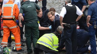 British MP Tobias Ellwood, centre, helps paramedics try to revive the stabbed officer.