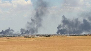 Smoke rises from the city of Manbij, Syria in June.