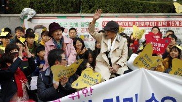 """Kim Bok-dong (hand raised), who was pressed into sex slavery by the Japanese army, greets the weekly """"Wednesday protest"""" which has been running for 23 years at Japan's embassy in Seoul."""