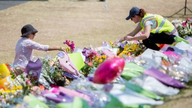People lay tributes at Dreamworld while a private memorial service was held inside on Friday.