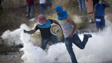 A Palestinian protester throws back a tear gas canister that was fired by Israeli troops during clashes near Ramallah, West Bank, on October Thursday.