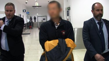 Hongchi Xiao, escorted by police at Sydney airport, was taken to Kogarah police station.