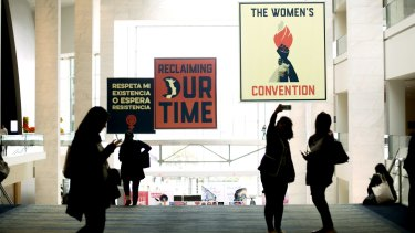 Attendees take a selfie photograph in front of signage displayed during the Women's Convention in Detroit, Michigan.