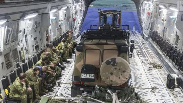 Members of Australia's reconnaisance and assessment team prepare to disembark a RAAF C-17A Globemaster aircraft at the Nausori International Airport in  Fiji.