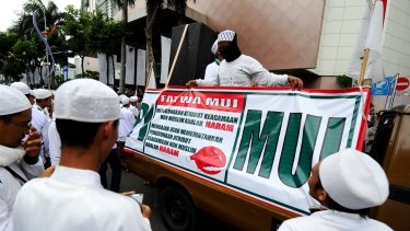 Islamic hardliners rally outside a shopping centre in Surabaya with a sign drawing attention to a fatwa issued by the Majelis Ulema Indonesia (MUI), an Islamic scholarly body, against Muslim staff wearing Christmas hats.