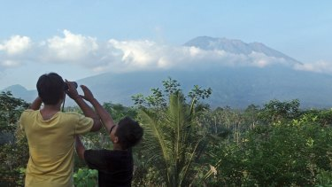 A man observes the Mount Agung with binoculars at a viewing point last week, as fears began to mount of an eruption.