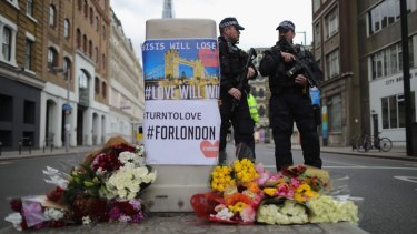 Armed police stand guard in front of floral tributes on Southwark Street near the scene of the terrorist attack.