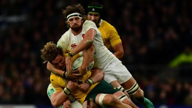 Michael Hooper of Australia (L) is tackled by Tom Wood of England (R) during the Old Mutual Wealth Series match between England and Australia at Twickenham.