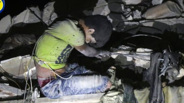 Rescue workers trying to remove a boy stuck in the debris of a building in  east Aleppo following an airstrike in Aleppo, Syria.