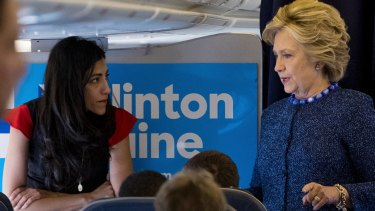 Hillary Clinton speaks with Huma Abedin aboard the campaign plane to Iowa on Friday.