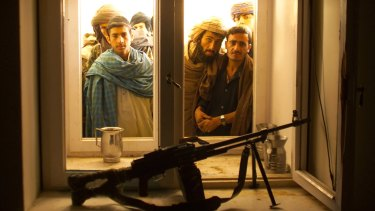 Afghans look through the window into the bedroom of Taliban leader Mullah Omar  after his overthrow in December 2001.
