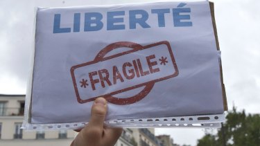 """A demonstrator holds a paper which reads, """"liberty, fragile"""", during a protest against the state of emergency in Paris in September."""