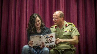 Teen author Jessica Love and her father, Australian Army Colonel Shaun Love, look at her book addressing parental deployment through a child's eyes.