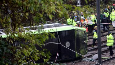 Emergency service workers attend the scene of the derailed tram in Croydon, south London.