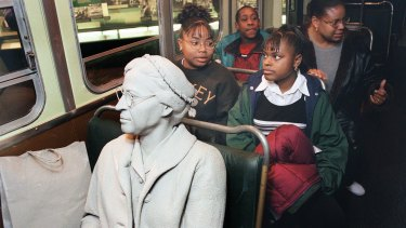 Visitors sit behind the figure of Rosa Parks, seated in the front of a bus at the National Civil Rights Museum in Memphis.