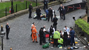 Emergency services attend to injured people outside the Palace of Westminster, London,
