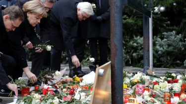 German Chancellor Angela Merkel and Foreign Minister Frank-Walter Steinmeier, right, lay flowers at the scene of the terror attack in Berlin.