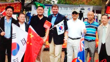 Craig Laundy (holding Chinese and Korean flags) and Yang Dongdong (far right) at a protest against Shinzo Abe's visit to the Yasukuni Shrine.