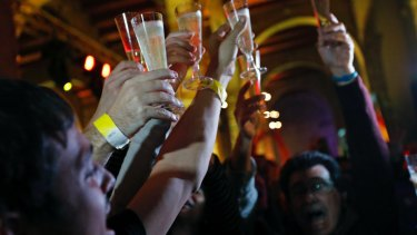 Catalan independence supporters make a toast as they celebrate at the Catalan National Assembly headquarters after results of the regional elections in Barcelona, Spain