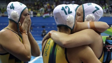 Heartache: Australia's players console each other after losing in a penalty shootout.