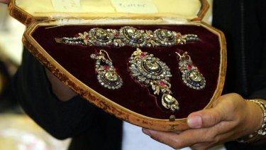 An officer of the Presidential Commission on Good Government (PCGG) shows diamond-studded items then valued at $US1.4 million during presentation of flamboyant former Philippine first lady Imelda Marcos' seized jewellery in Manila, in 2005.