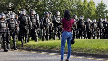 A protester watches as police in riot gear clear the street of protesters in front of the Baton Rouge Police Department headquarters.