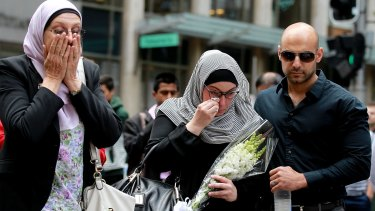 Members of the Muslim community lay flowers at Martin Place after two people and a gunman died when the siege ended Tuesday morning.