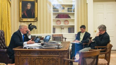 Happier times: Trump takes a call with former national security advisor Michael Flynn and Stephen Bannon in attendance, in the Oval Office.