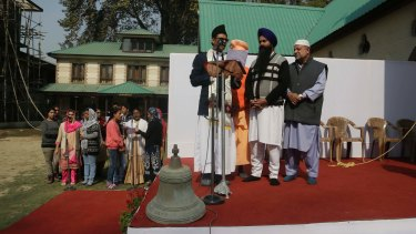 The old bell that was removed takes centre stage as people from various faiths including Muslims, Hindus and Sikhs participate in the installation of the new bell at the Holy Family Catholic Church in Srinagar.