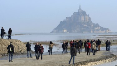 People gather ahead of a high tide submerging a narrow causeway leading to the Mont Saint-Michel, on France's northern coast.