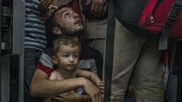 A refugee holds his son as they wait for a train to leave Budapest, Hungary, on September 3.
