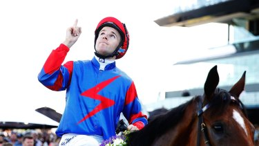 Jockey Tommy Berry, with what has become a customary salute to his twin brother, Nathan.