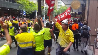 Construction workers boo and wave flags as John Howard is escorted down the footpath.