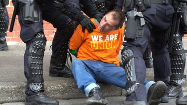 A man is detained by police.