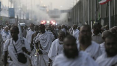 Pilgrims walk by the site where hundreds were crushed and trampled to death during the annual haj pilgrimage in Mina, Saudi Arabia.