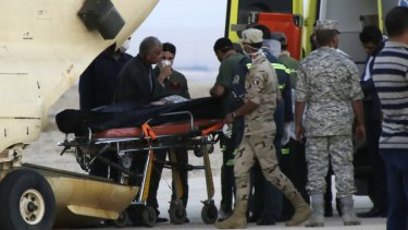 Egyptian emergency workers unload bodies of victims from the crash of a Russian aircraft carrying 217 passengers and 7 crew.