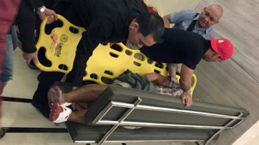 An injured man is placed on a stretcher after explosions rang out in Manila.