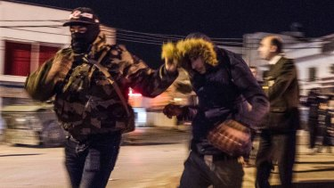 A riot policeman drags away a demonstrator during protests against the government's austerity measures in Tunis.