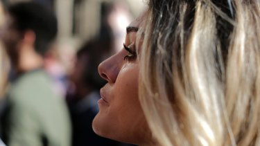 A woman cries as she attends a vigil in Albert Square, Manchester, England.