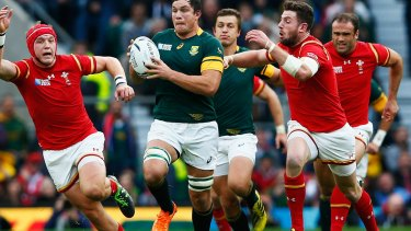 South Africa's Francois Louw is tackled by Alex Cuthbert of Wales.