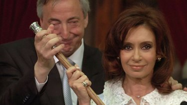 Cristina Fernandez grabs the presidential cane from her husband and predecessor Nestor Kirchner, after being sworn in as Argentina's first elected female president in 2007.