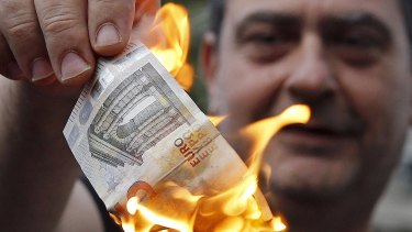 An anti-austerity protester burns a euro note during a demonstration outside the European Union offices in Athens, Greece.