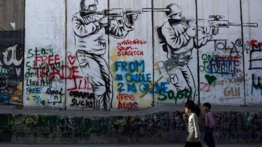 Children walk past graffiti on the Palestinian side of the separation wall in the West Bank.