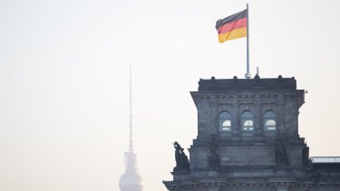 A German national flag flies above the Reichstag in Berlin, Germany.