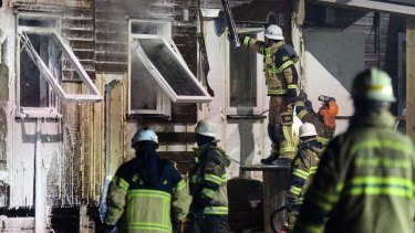 Firefighters extinguish a fire after evacuating residents from the refugee accommodation in Fagersjo, south of Stockholm, Sweden.