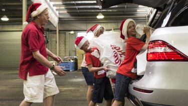 The Petersen family pack their car as part of The Smith Family Christmas delivery day.